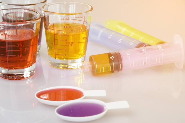 Medicinal cup, oral syringe and teaspoon filled with oral syrup medicine.