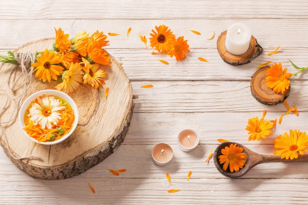 Medicinal flowers of calendula on white wood
