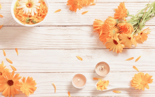 Medicinal flowers of calendula on white wooden background