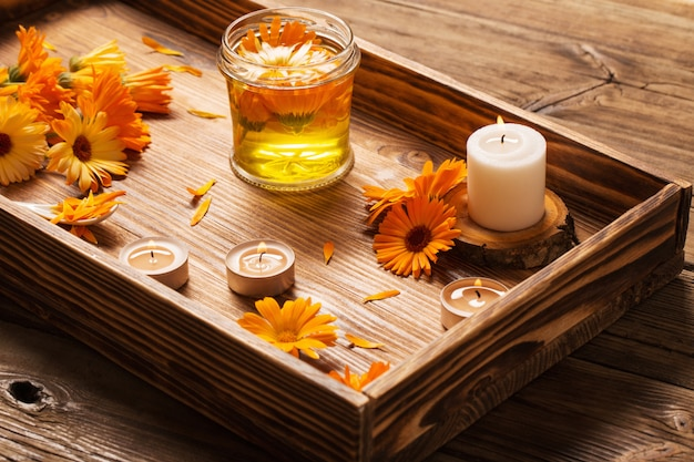 Medicinal flowers of calendula with burning candles on dark woo