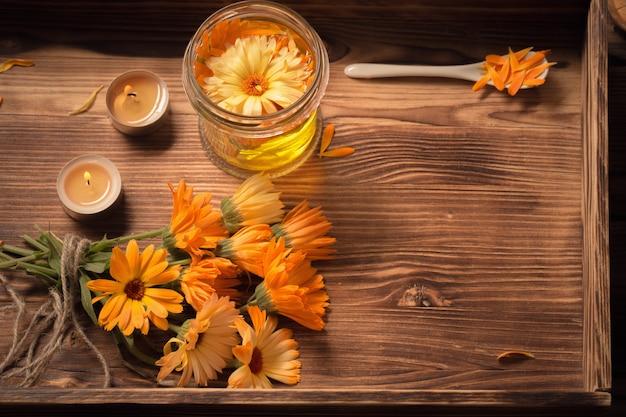 Лекарственные цветы календулы и ароматическое масло с зажженными свечами на подносе на темном дереве