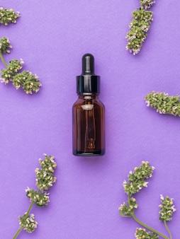 Лекарственные травы и терапевтический флакон с пипеткой на фиолетовом фоне. плоская планировка.