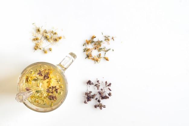 Лекарственные травы и чай в чашке на белом