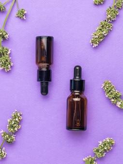 Лекарственные травы и две бутылки с лекарством на фиолетовом фоне. концепция лечения и ухода за телом с помощью натуральных средств. плоская планировка.