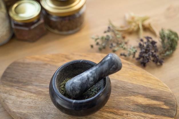 Лекарственные травы, ступка целебных трав, пакетик и бутылка здоровых лекарств на деревянном столе. травяной медицины. вид сверху, плоская планировка.