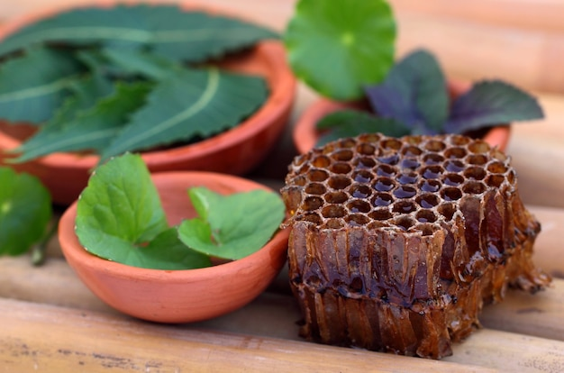 Medicinal herbs with honey comb on a bamboo surface