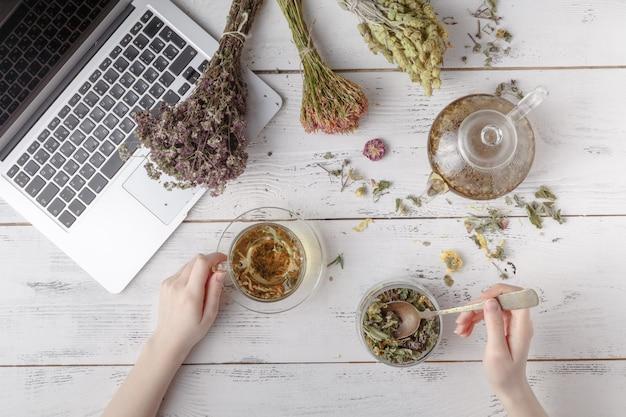 木製のテーブルのレシピと薬草。フラットレイ