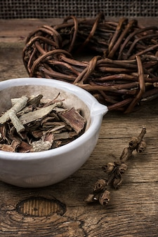 Medicinal licorice rolled in  coil and aspen bark on wooden background.