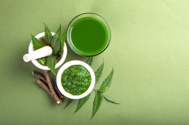 Medicinal neem leaves in mortar and pestle with neem paste, juice and twigs on green surface