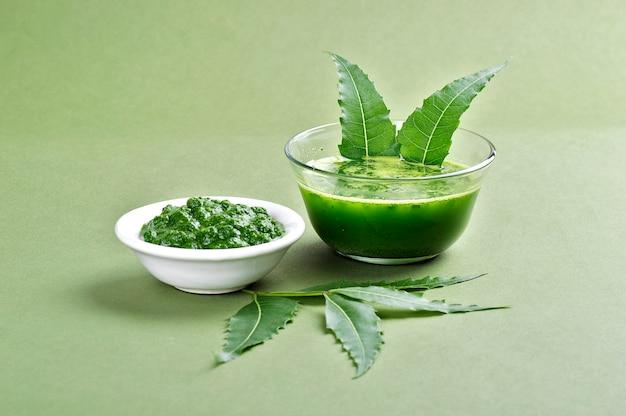 Лекарственная паста из листьев нима и сок с листьями на зеленом