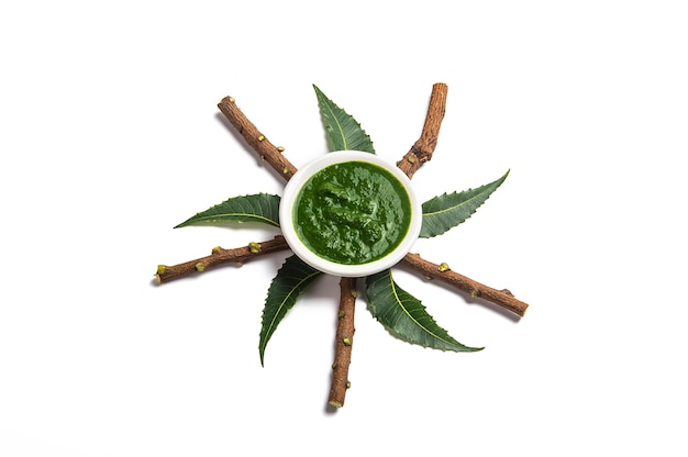 Medicinal neem leaves with paste in bowl and twigs on white background