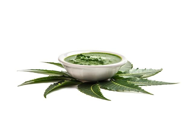 Лекарственные листья нима с пастой в миске на белой поверхности.