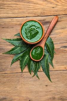 Лекарственные листья нима с пастой на деревянной поверхности