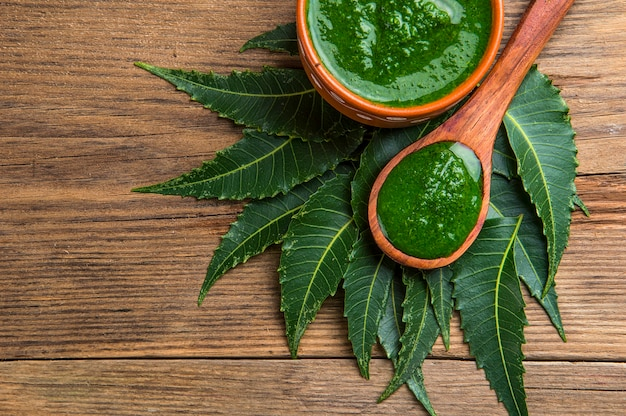 Medicinal neem leaves with paste on wooden surface