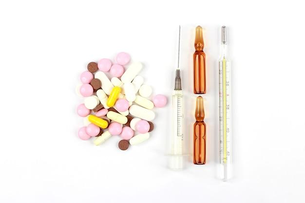 약용 정제, 주사용 앰플, 온도계, 흰색 배경에 주사기