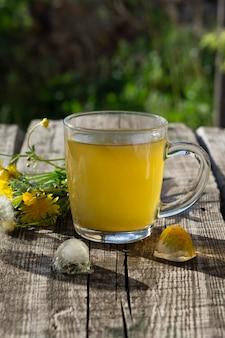 Лечебный чай из одуванчика в стеклянной чашке и цветок одуванчика на деревянном деревенском столе со льдом