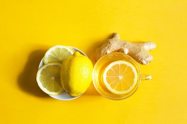 Лечебный чай в чашке, имбирь, лимон укрепляют иммунитет в холодное время года. витаминный напиток для здоровья и ингредиенты на желтом фоне подсветки. копировать пространство, категорически