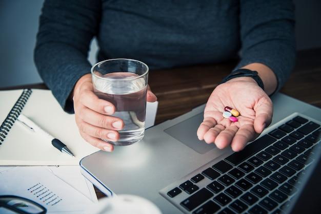 薬と病気のための女性の手の中に水の入ったグラス