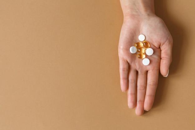 医学とヘルスケア。女性の手のひらにビタミンが入った錠剤やカプセル。ダイエットと健康的な食事