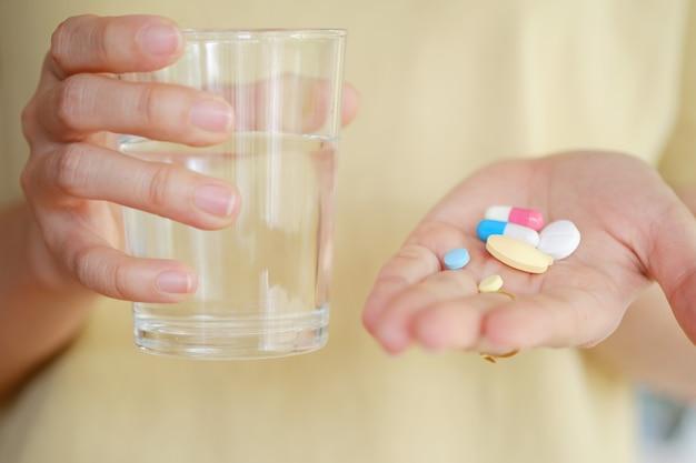 病気を治療するために食べるための女性の手の薬と水。ヘルスケアの概念。