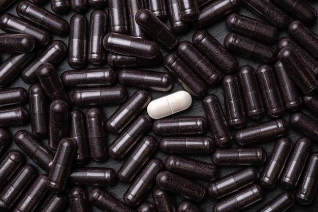 Предпосылка медицины из связки черных пилюль и одной белой капсулы посередине, макроса. производство лекарств.