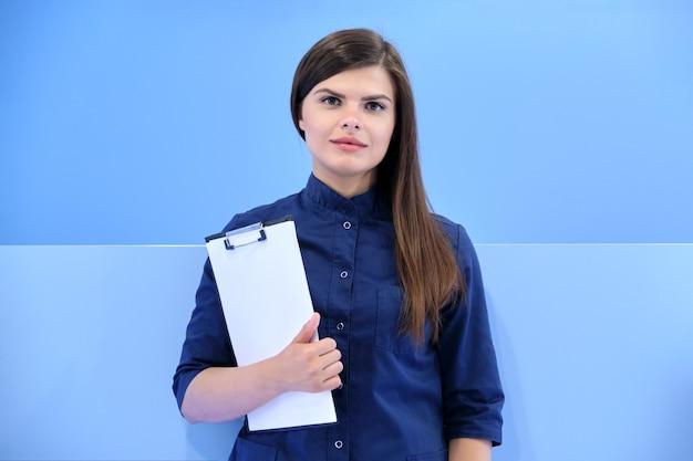 의학, 미용, 치과, 미용, 성형 외과, 클리닉 배경에서 카메라를 보고 있는 클립보드와 함께 파란색 유니폼을 입은 젊은 웃는 여성의 비즈니스 초상화