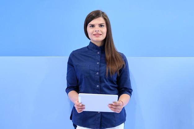 의학, 미용, 치과, 미용, 성형 수술, 클리닉 배경에서 카메라를 보고 있는 디지털 태블릿으로 파란색 유니폼을 입은 젊은 웃는 여성의 비즈니스 초상화
