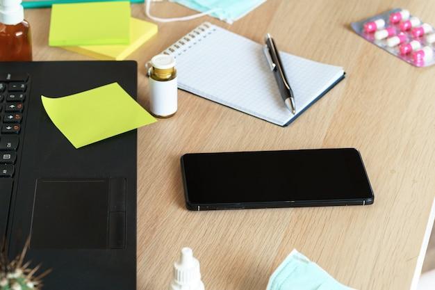 ノートパソコンとオフィスのテーブルに薬瓶をクローズアップ