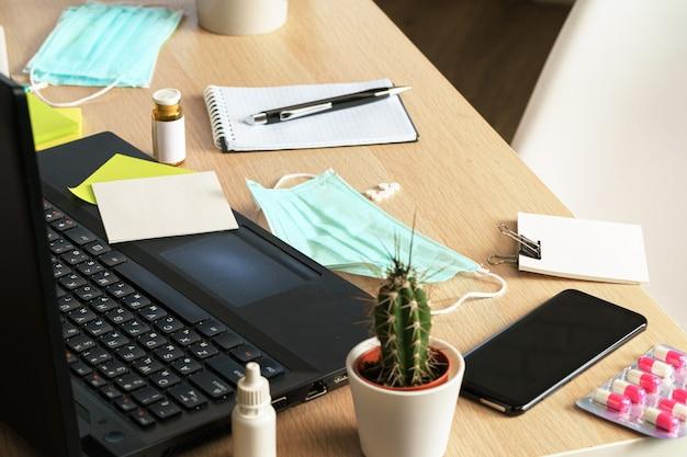 ノートパソコンとオフィスのテーブルの上の薬瓶