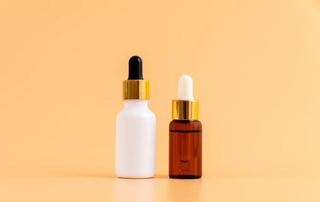 薬瓶を置き、オレンジ色の背景にモックアップ用の空白のラベルパッケージ。自然美容製品のコンセプト。
