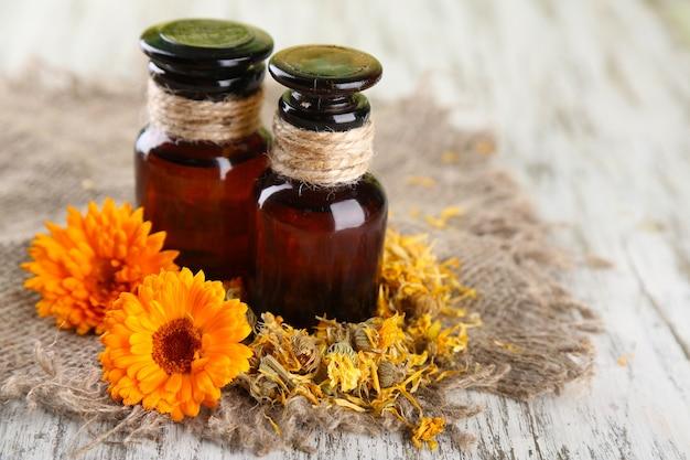 Бутылки с лекарствами и цветы календулы на деревянном