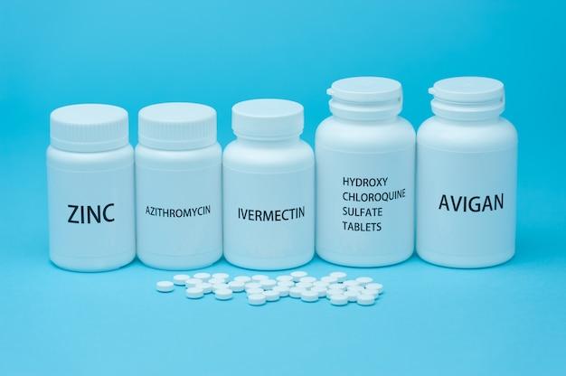 Бутылочки с лекарствами для лечения covid-19. рассыпанные таблетки. изолированные на синем фоне.