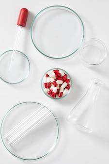 건강 치료를 위해 흰색 배경에 실험실 장비와 약 캡슐