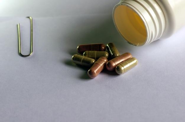 メモ用の薬のカプセルとホワイトペーパー