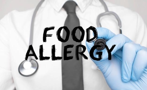 의학 개념입니다. 의사는 음식 알레르기라는 단어를 씁니다. 흰색 배경에 고립 된 마커를 들고 손의 이미지.