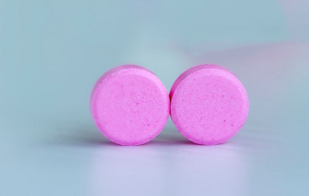 Medicine concept; pink pills with white background