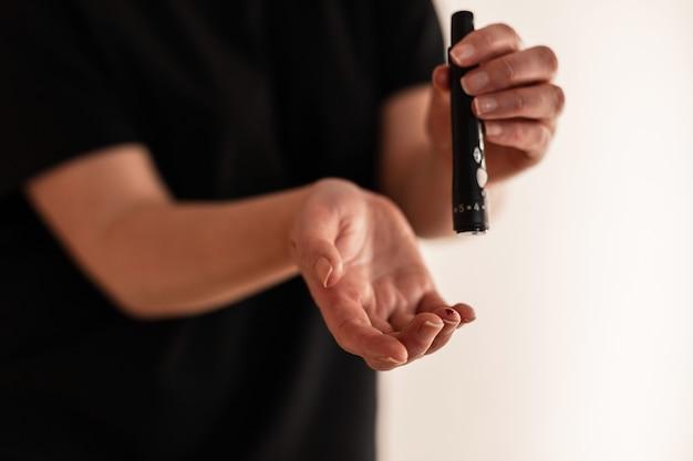 Медицина, диабет, гликемия, здравоохранение и люди концепция - крупный план женщины, использующей ланцетник на пальце для проверки уровня сахара в крови с помощью глюкометра