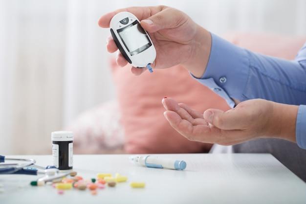 医学、糖尿病、血糖、医療、人々の概念-テストストライプを持つ男性の指のクローズアップ