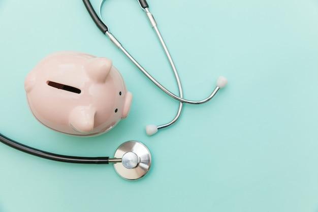 의학 의사 장비 청진 기 또는 phonendoscope 및 유행 파스텔 파란색 배경에 고립 된 돼지 저금통