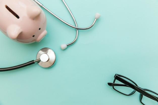 의학 의사 장비 청진 기 또는 phonendoscope 돼지 저금통 안경 유행 파스텔 파란색 배경에 고립