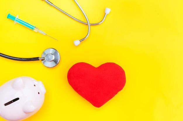 의학 의사 장비 청진기 또는 phonendoscope 돼지 저금통 붉은 심장 주사기 노란색 배경에 고립