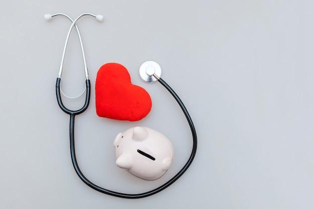 의학 의사 장비 청진 돼지 저금통과 붉은 심장 흰색 배경에 고립