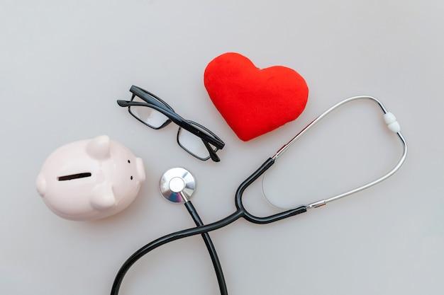 의학 의사 장비 청진 돼지 저금통 안경 및 흰색 배경에 고립 된 붉은 심장