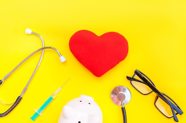 Medicine doctor equipment stethoscope piggy bank glasses red heart syringe isolated on yellow table