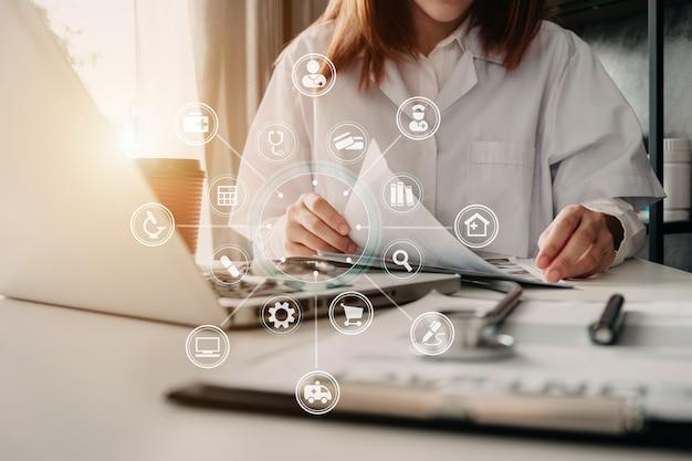 의학 의사는 보고서와 노트북 컴퓨터 인터페이스를 의료 네트워크 개념으로 사용합니다.