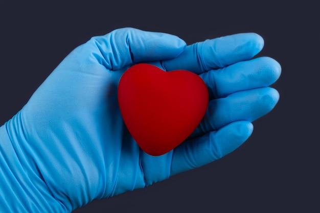 赤いハートの形を手で押し医学博士