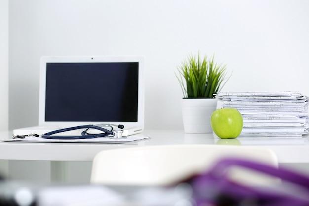Рабочий стол врача врача. ноутбук, документы, зеленое яблоко и стетоскоп, лежащие на столе в кабинете врача. здравоохранение и медицинская концепция