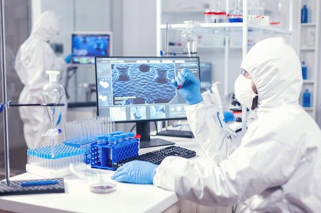 안면 마스크와 코발을 가진 의학 엔지니어가 혈액 샘플 실험실을 보고 있습니다. 다양한 박테리아와 조직을 다루는 의사, covid19에 대한 항생제에 대한 제약 연구.