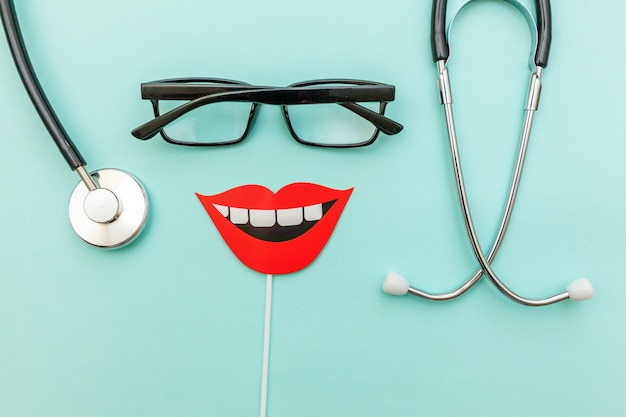 Medicine equipment stethoscope glasses sign of smile teeth isolated on trendy pastel blue