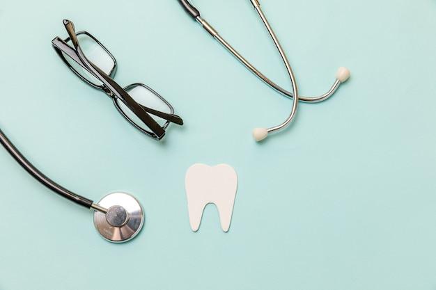 의학 장비 청진기 흰색 건강한 치아 안경 파스텔 파란색 배경에 고립 프리미엄 사진